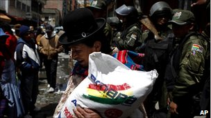 A woman carries a bag of sugar bought at a government subsidized market in La Paz as riot police stand guard