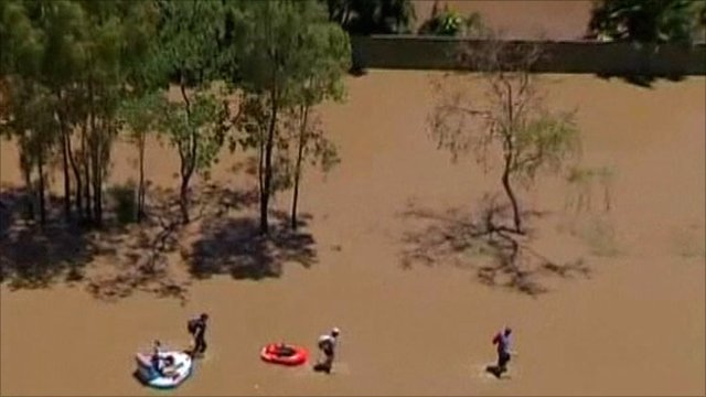 People wading through floodwater in Queensland