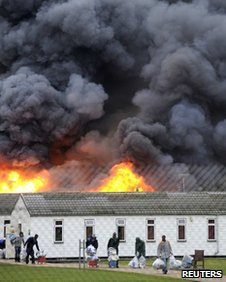 Inmates carry their possessions and walk from burning buildings during a riot at Ford open Prison, near Arundel, on 1 January 2011