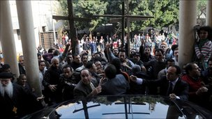 Protesters crowd round a vehicle carrying Egyptian Grand Imam of Al-Azhar Ahmed al-Tayeb at the al-Abasseya Cathedra in Cairo, 2 January 2011.