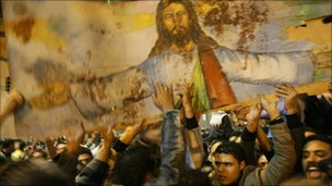Egyptian Christians hold a blood-stained portrait of Jesus Christ during a protest in Alexandria, 2 January