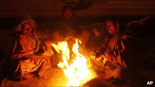 People huddle around a fire during a cold snap in India