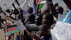 Pro-separation activists hold signs and chant pro-independence slogans outside Juba airport in southern Sudan as they await the arrival of Sudanese President Omar al-Bashir.