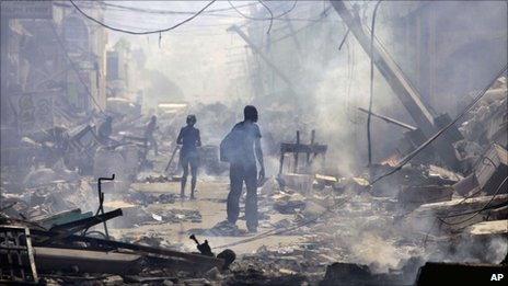 People walk down a street amid rubble in Port-au-Prince, in the immediate aftermath of the January 2010 earthquake.