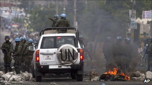 UN peacekeepers pass through a barricade set by protesters in Port-au-Prince, 10 December 2010.