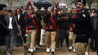 Pakistani police guards carrying the coffin of Salman Taseer 
