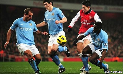 Arsenal's Samir Nasri is crowded out by Man City players