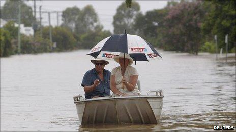 A couple make their way through Depot Hill, Rockhampton, as rain falls on 6 Jan 2010
