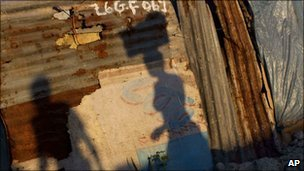 Shadows of people on a wall in a camp for earthquake survivors in Port-au-Prince