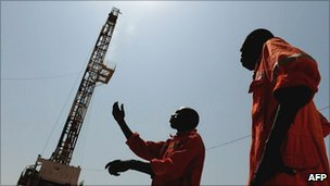 Two oil workers stand on the drilling site in Unity State, Southern Sudan on 11 November 2010