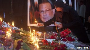 A woman places a candle by a photo of Salman Taseer in Lahore, Pakistan (6 Jan 2011)