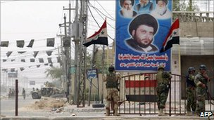 Iraqi soldiers walk past a poster of Moqtada Sadr in Basra (April 2008)