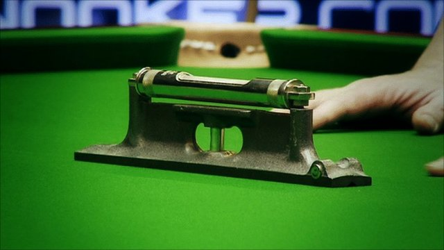 An expert uses a device to measure whether a snooker table is flat