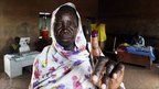 A southern Sudanese woman shows her inked finger after voting in the independence referendum at a polling centre in Khartoum, 10 January 2011