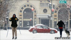 A man in the downtown area of the town of Asheville in North Carolina skiing on a road