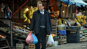 A man holds plastic bags in Quba market in Algiers, on January 10, 2011.