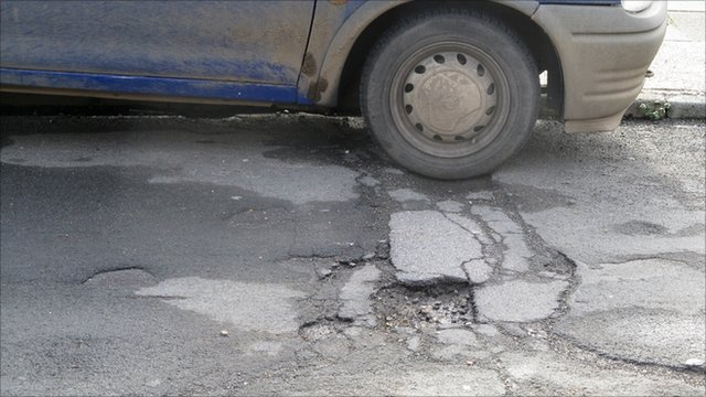 Pothole and car wheel