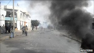 Smoke is seen in a street in Regueb, where funeral processions were held for people shot in recent clashes with police,  on 10 January  2011