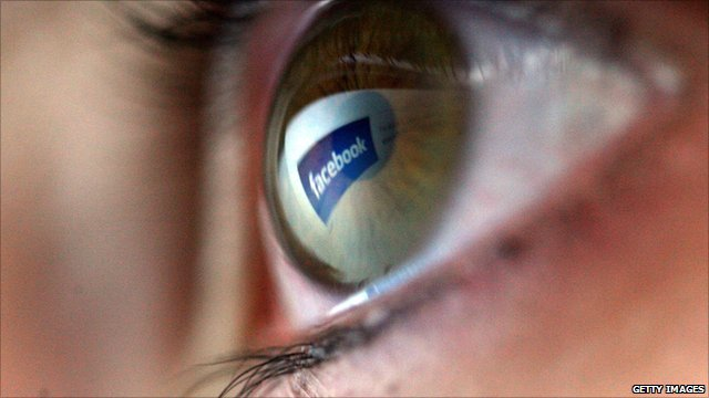 A woman's eye with a Facebook logo reflection