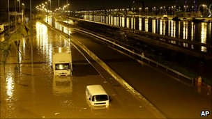 Abandoned vehicles sit in a flooded avenue after heavy rains in Sao Paulo
