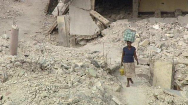 Woman walking through rubble in Haiti
