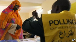 A polling centre official explains to a Southern Sudanese woman the two voting signs contained in the ballot, separation and unity, at a polling centre during the third day of the referendum in the city of Um Durman, Sudan