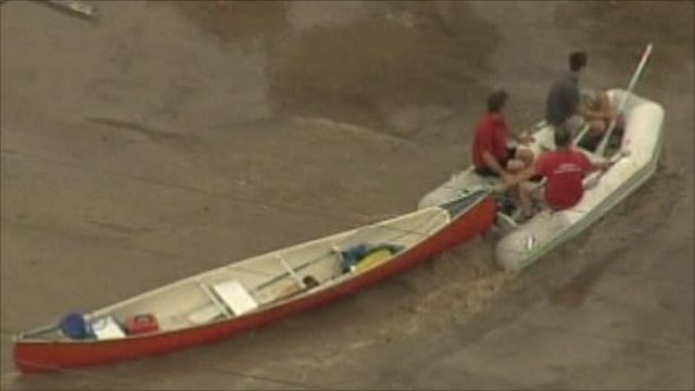 People towing a boat with a dighy through flood water