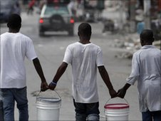 Men walk through streets in Port-au-Prince carrying water
