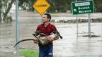 A man carries a kangaroo after rescuing it from floodwaters in Ipswich, near Brisbane. Photo: 12 January 2011