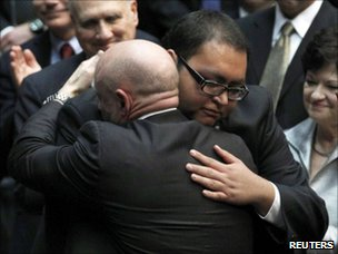Daniel Hernandez is hugged by Rep Giffords' husband at the McKale Memorial Center in Tucson (12 January 2011)