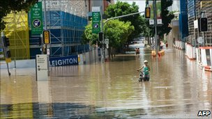 A cyclist pushes her bicycle down a flooded Brisbane street on 13 January 2010