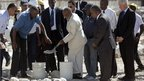 Former US President Bill Clinton (R) watches as Haitian President Rene Preval (C) shovels cement onto the first stone laid for a memorial park in Port-au-Prince