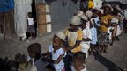 Children line up at displaced persons camp in Port-au-Prince before attending a ceremony marking the earthquake's anniversary