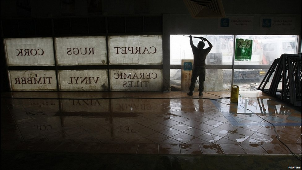 A man uses a hose to clean a flood damaged carpet shop in the town of Ipswich