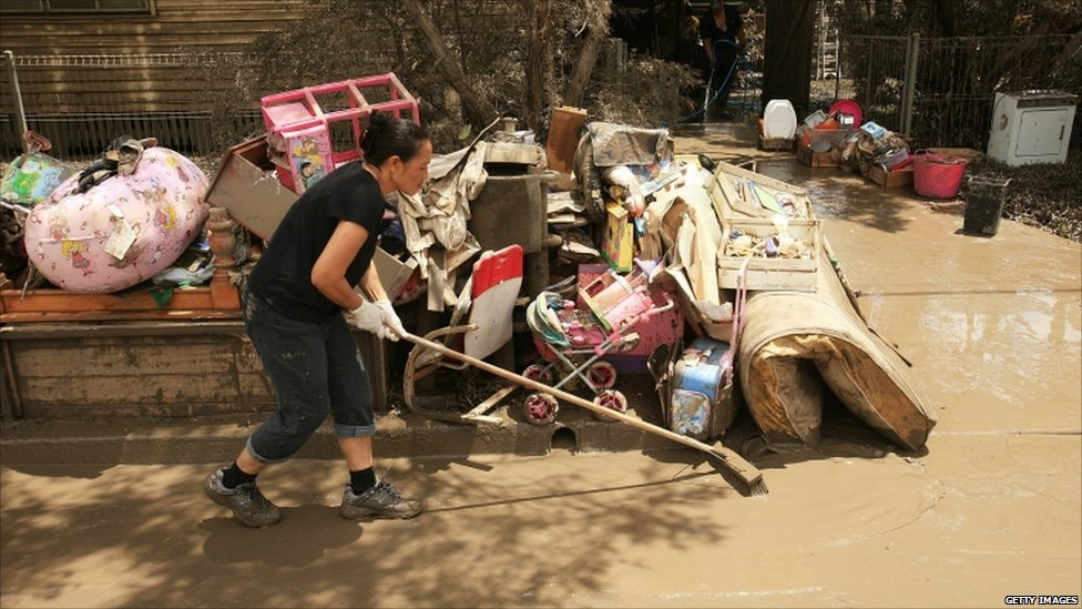 A volunteer helps clear mud from the front of a property damaged by flood waters
