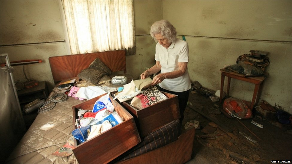An elderly resident of Fairfield sorts through items damaged by flood waters in her home