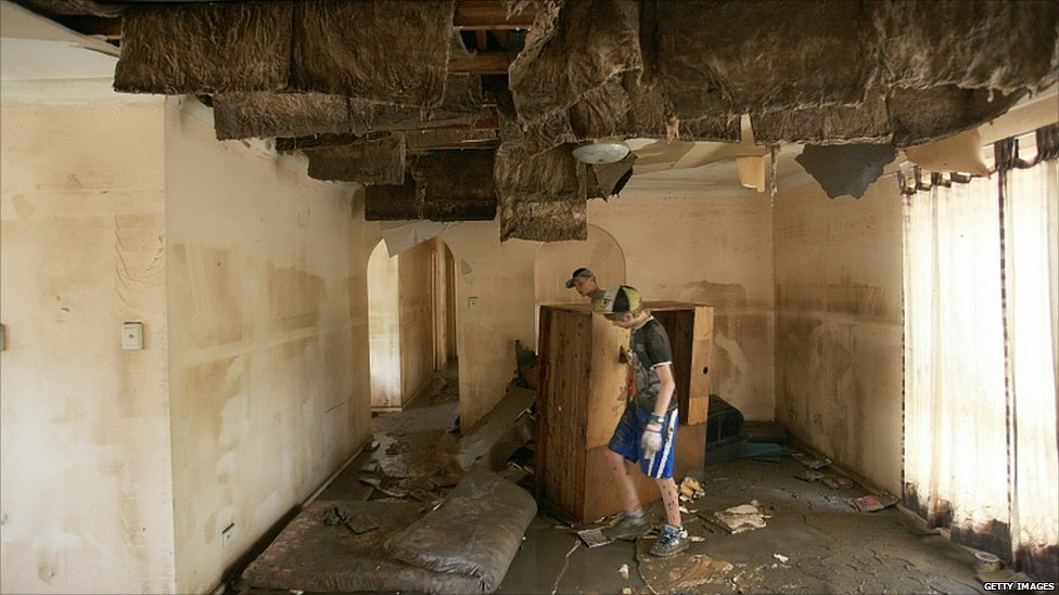 Volunteers help clear a home which was completely submerged by flood waters