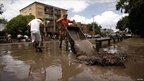 Volunteers tip barrow loads of mud from riverfront houses into the Brisbane River
