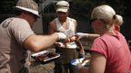 Residents from an unaffected area of Brisbane hand out a free sausage sandwich to a man cleaning a damaged house