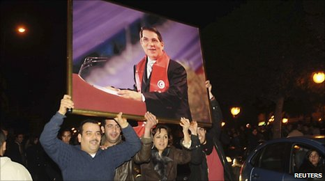 Supporters of President Ben Ali hold up a portrait of him at a rally in Tunis on 13 January 2011