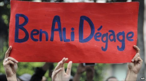 "Protesters in Tunis hold up a banner saying: ""Ben Ali Get Out"" (14 January 2011)"
