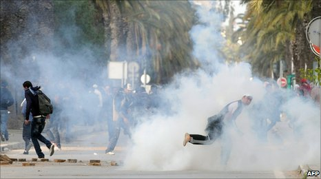 Youths throw stones at police after tear gas is fired in central Tunis (14 January 2011)