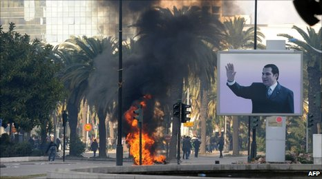 A fire near a portrait of President Zine al-Abidine Ben Ali in Tunis (14 January 2011)