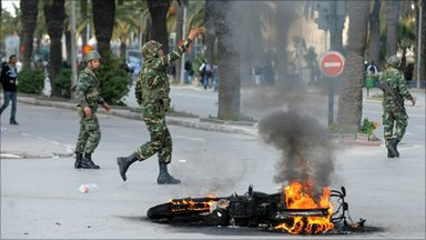 Tunisian troops and burning motorcycle, Tunis, 14 January 2011
