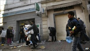 People take food and other goods from a destroyed store in Tunis, Saturday, Jan. 15. 2011.