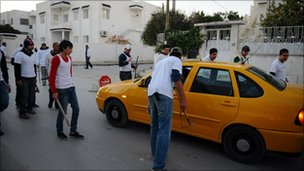 Tunisian men holding metal bars and sticks speak to a driver near Tunis on 15 January 2011. 
