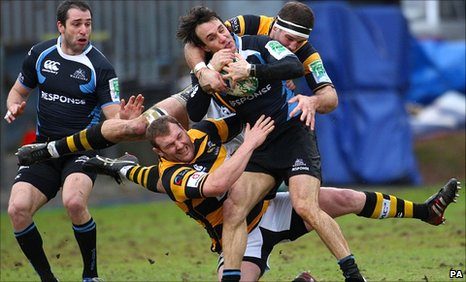 Glasgow's Bernardo Stortoni is tackled by Wasps' James Cannon and Andy Powell