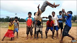 Sri Lankan flood-affected children play for the camera at a relief camp in the eastern Sri Lankan town of Batticaloa on 14 January 2011