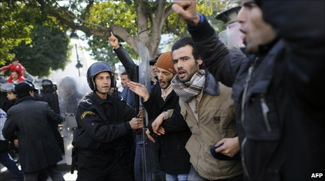 A policeman holds back protesters in Tunis, Tunisia (17 Jan 2011)