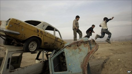 Afghan boys jump down from old vehicles in Kabul in January 2010